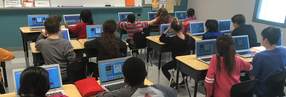 students using laptops in a classroom.